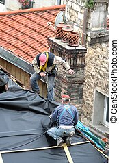 Two carpenters at work on a house roof