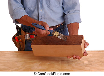Woodworker applying stain to a wooden box isolated over...