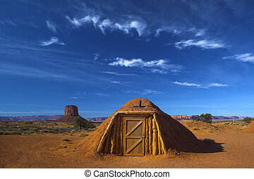 Hogan, the traditional Navajo red clay earth house, with...