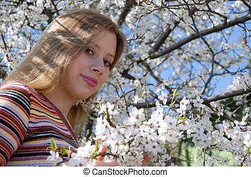 Pretty girl on blossoming tree background