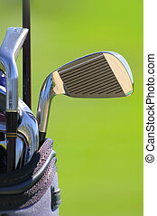 Golf Clubs - shallow depth of feald of golf clubs with green...