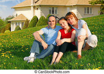 Family at a house - Portrait of a happy family of three on...