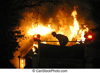 house fire - An Edmonton,Alberta firefighter stands atop a...