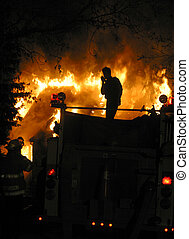 house fire - An Edmonton,Alberta firefighter talks on a...