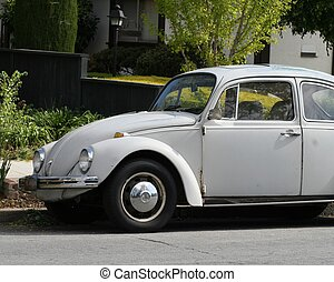 White Volkswagen Beetle - Classic Volkswagen bug parked on a...
