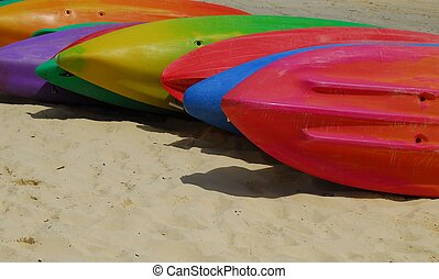Colourful Kayaks - Multi coloured kayaks side by side on a...