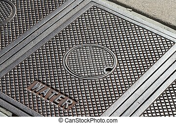 Manhole Cover Water - A manhole cover on the sidewalk for...