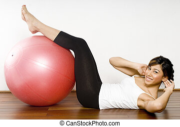 Fitball Crunch - A young asian woman performing an abdominal...