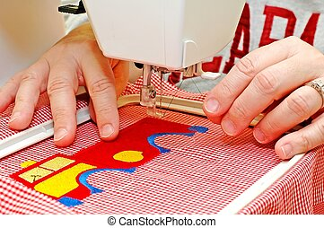 Sewing - Female operating embroidery machine.