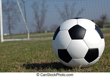 Soccer ball on field with goal in background