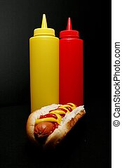 Hot Dog  - Hot dog with ketchup and mustard bottles.