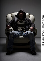dangerous man sitting in white chair - dark portrait of...