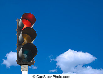 Traffic lights - red light is on - in front of blue sky