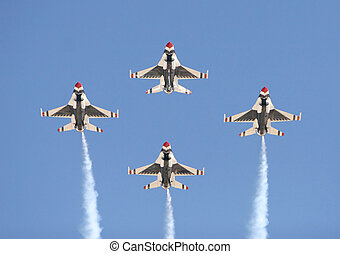 Four fighter jets flying in formation against a clear blue...