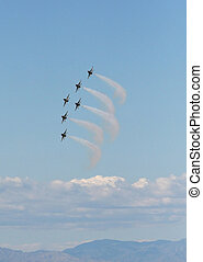Six fighter jets flying in formation against a clear blue...