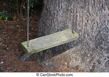 Wooden Swing - Wooden swing hanging from a tree