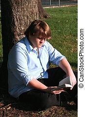 Teen Boy Reading In Park