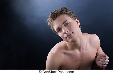 Young beautiful man - Young man posing against dark...