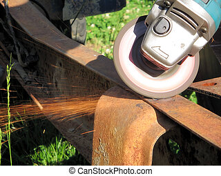 angle grinder working on rusty frame