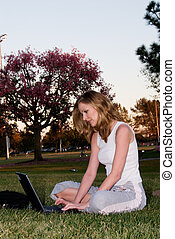 Working outdoors - Blonde woman working on laptop while...