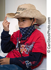 Little cowboy - Young asian boy sitting on a white sofa...