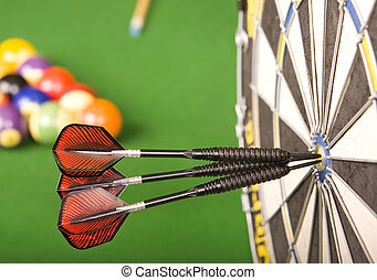Games room - Three darts in a dart board with a pool game in...