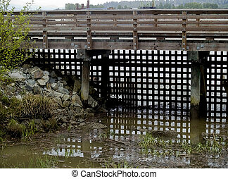 Latticework Bridge - Wooden bridge over stream with lattice...