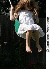 Girl On Swing - 5 year old girl swinging on a green swing,...