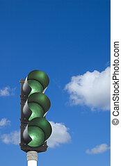 Traffic lights - all lights green in front of blue sky