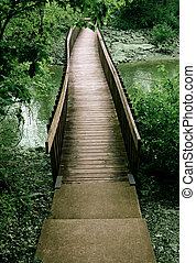 Bridge out of the woods - Brown wooden bridge through green...