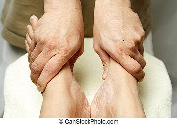 Foot massage - A masseuse massaging the feet of a woman