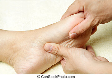 Foot massage - A masseuse massaging the foot of a woman