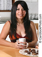 Woman relaxing with coffee - A pretty woman sitting down at...