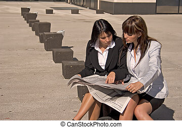 businesswoman looking at a newspaper - businesswomen sitted...