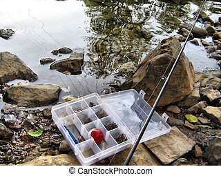tackle 6 - fishing tackle and pole sitting on river bank