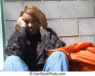 Homeless Woman - Woman sitting against a wall