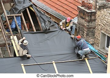 Carpenters at work - Three carpenters working on the roof of...