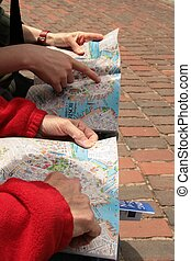 Directions X 2 - 2 people with 2 maps discussing sites on a...