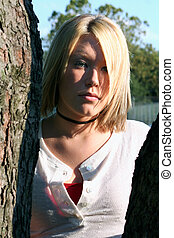 In The Shadows - Serious young blond woman, standing in the...