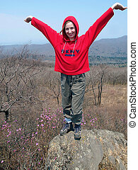 hiking girl  on the rock with arms wide open