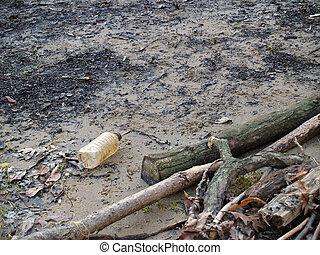 litter - old plastic bottle washed up on river bank