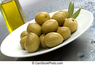 olive fruit on a plate with olive oil in background
