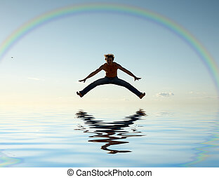 jump over water under rainbow - sporty man jumping under big...