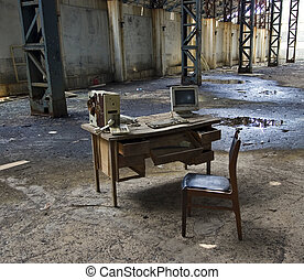 Abandoned computer workstation in an old factory