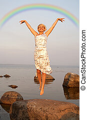 flight under rainbow - lovely blond jumping at the seashore...
