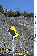 Falling rocks sign on the mountain slope - Yellow falling...