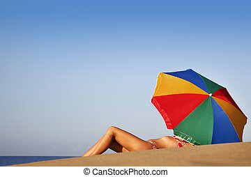 Summer Beach Babe - Pretty woman under parasol on the beach