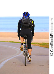 Riding bicycle - A person riding a bicycle on a seashore...