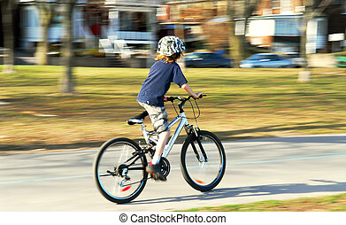 Boy riding a bike - Panning shot of a boy riding a bicycle,...