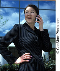 business woman cell phone - A young business woman standing...